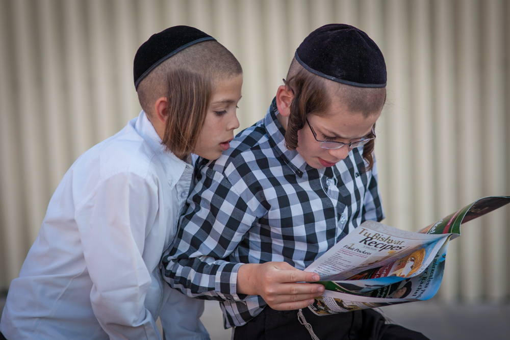 Two ortodox Jewish boys studying a magazine close to the Western wall in Jerusalem. Photo: John Einar Sandvand